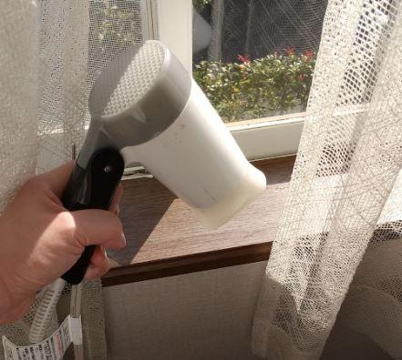 窓枠の木の表面の保護シートをドライヤーで熱している様子